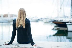ung flicka sitter i hamnen foto