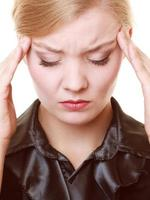 huvudvärk. kvinna som lider av huvudvärk isolerad. foto