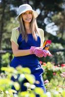 leende ung flicka i uniform på trädgårdsskötseln foto