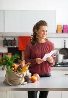 porträtt av lycklig hemmafru som håller livsmedelsbutikcheck foto