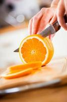 kvinnans händer som klipper orange foto