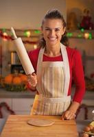 hemmafru med brödkavel i juldekorerat kök foto