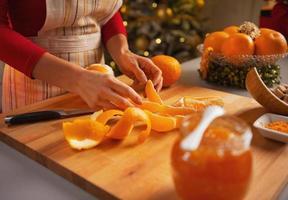 närbild på ung hemmafru som gör apelsin sylt foto