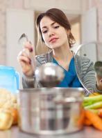 vacker kvinna matlagning med sleven foto