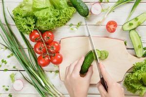 händer skära gurka för sallad på trä bakgrund, ovanifrån foto