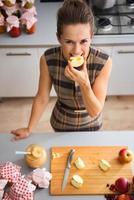 glad kvinna som biter i äpplekvartalet i köket foto