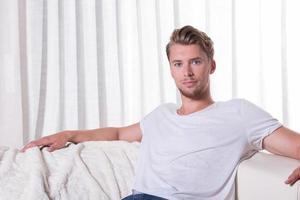 porträtt ung man sitter på soffan foto