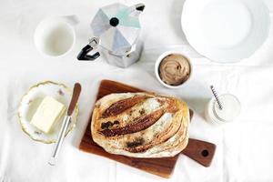 frukost med surdeigsbrödmuff och smör med kaffe foto