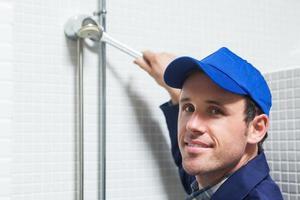 glad rörmokare som reparerar duschhuvudet foto