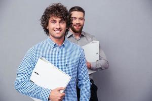 två glada affärsmän som rymmer mappar foto
