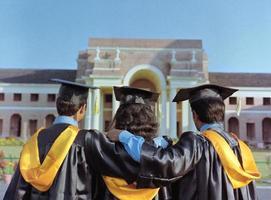 team av studenter som tittar på sitt universitet i examen klänning. foto