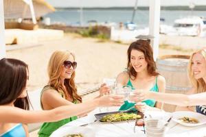leende flickor tittar på surfplattan på café foto