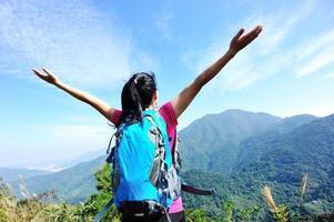 jublande vandringskvinna vid bergstoppen foto