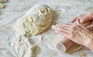 kök, matlagning pajer med deg på bordet foto