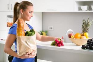 kvinna med en shoppingväska full av färsk mat foto