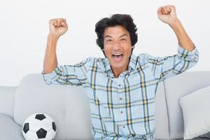 fotbollsfan jublande medan du tittar på tv foto