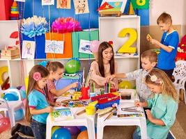 barn som håller färgat papper och lim på bordet i dagis foto