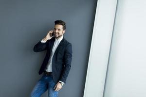 ung man med mobiltelefon på kontoret foto
