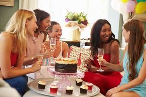 grupp kvinnliga vänner som firar födelsedag hemma