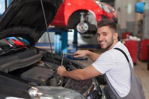 glad mekaniker med hjälp av en spärrnyckel foto