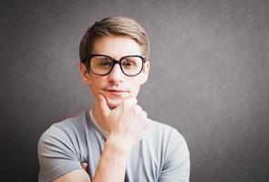 porträtt av en man med glasögon som står mot den grå väggen, foto