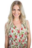 glad blondin som bär blommig klänning poserar foto