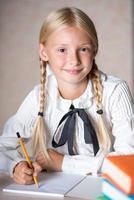 glad skolflicka som skriver i anteckningsboken foto