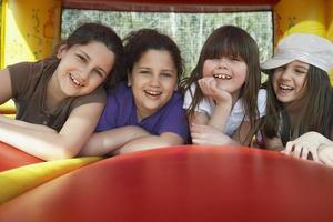 glada flickor som ligger i hoppslottet foto
