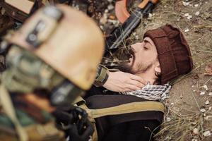 soldater teamläkare hjälper den sårade talibansoldaten foto