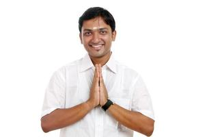 glad indisk traditionell ung man som ger gest foto