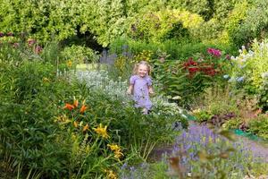glad liten flicka bland blommor i park foto