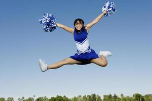 cheerleader utför cheer i luften foto