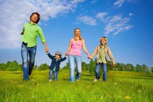 glada föräldrar som går med pojkar i park foto