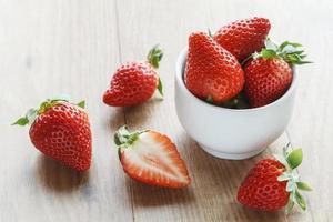färska jordgubbar, hackade, skål på trä foto