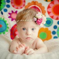 glad liten baby flicka med downs syndrom foto