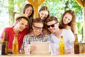 vänner som dricker och använder surfplatta foto