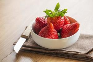 färska jordgubbar i skål, servett och kniv foto