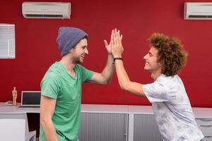 avslappnade unga affärsmän med höga fiving på kontoret foto