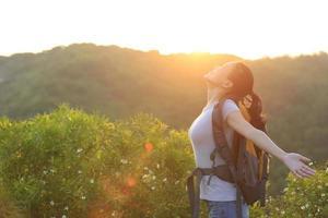jublande kvinna vandrare öppna armar med soluppgång foto