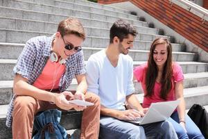 glada studenter som använder digital surfplatta