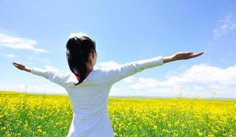 jublande kvinna öppna armar på cole blommor fält foto