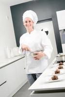 glad professionell bakverkskock för ung kvinna på jobbet foto