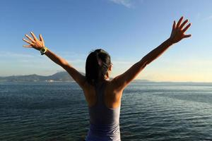 jublande öppna armar för ung kvinna vid soluppgången vid havet foto
