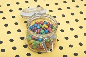 färgglada godisar i glasburk på polka dot servett foto