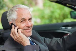 glad affärsman i telefon som kör dyra cabriolet