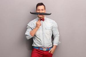 glad ung man med en enorm falsk mustasch foto
