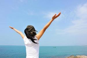 jublande kvinna öppna armar vid havet, sommarlovet foto