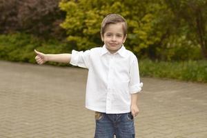 porträtt av gladlynt pojke visar tummen upp gest foto
