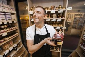 glad försäljare som håller burk med sylt i livsmedelsbutik foto