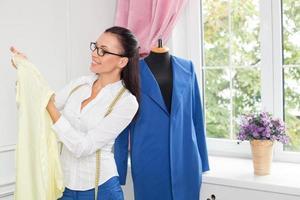 glad kläddesigner kontrollerar kvaliteten på sitt arbete foto